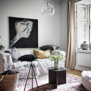 This is an example of a scandi living room in Gothenburg with white walls, light hardwood flooring and no fireplace.