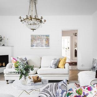 Exempel på ett klassiskt separat vardagsrum, med vita väggar, ljust trägolv och en öppen hörnspis