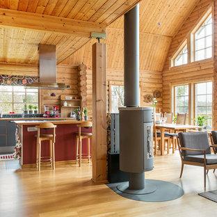Inspiration för ett mycket stort lantligt allrum med öppen planlösning, med bruna väggar, ljust trägolv och en öppen vedspis