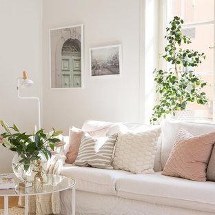 Bild på ett skandinaviskt vardagsrum, med vita väggar och mellanmörkt trägolv