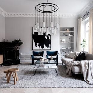 Inspiration för ett funkis vardagsrum, med grå väggar, ljust trägolv, en öppen hörnspis, en väggmonterad TV och grått golv