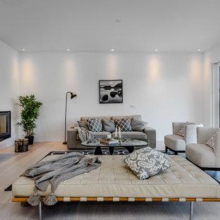 Bild på ett mellanstort nordiskt vardagsrum, med vita väggar, ljust trägolv och beiget golv