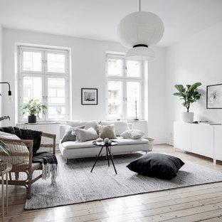 Bild på ett minimalistiskt separat vardagsrum, med ett finrum, vita väggar och ljust trägolv