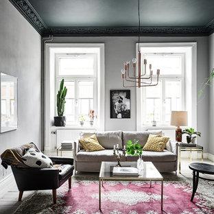 Foto på ett mellanstort eklektiskt vardagsrum, med ett finrum, grå väggar och ljust trägolv
