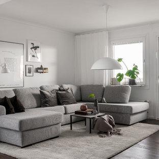 Minimalistisk inredning av ett vardagsrum, med vita väggar, mörkt trägolv och brunt golv