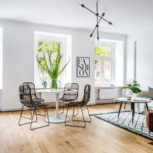 Foto på ett stort skandinaviskt allrum med öppen planlösning, med vita väggar och ljust trägolv