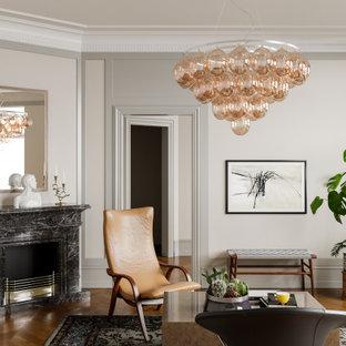 Modern inredning av ett stort vardagsrum, med grå väggar, mellanmörkt trägolv, en standard öppen spis, en spiselkrans i trä och brunt golv