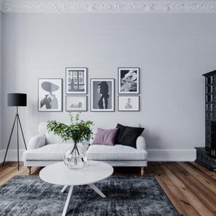 Inspiration för mellanstora moderna vardagsrum, med grå väggar, en öppen hörnspis, en spiselkrans i metall och brunt golv