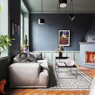 Esempio di un soggiorno moderno di medie dimensioni e aperto con pareti blu, pavimento in legno massello medio, camino ad angolo, nessuna TV e sala formale