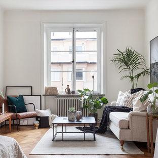 Idéer för ett mellanstort skandinaviskt allrum med öppen planlösning, med vita väggar, mellanmörkt trägolv och ett finrum