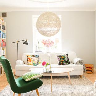 Idéer för nordiska vardagsrum, med ljust trägolv, ett bibliotek och grå väggar