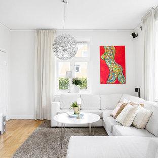 Foto på ett stort funkis allrum med öppen planlösning, med ett finrum, vita väggar och ljust trägolv