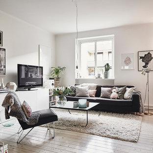 Imagen de salón abierto, escandinavo, de tamaño medio, sin chimenea, con paredes blancas, suelo de madera pintada y televisor independiente