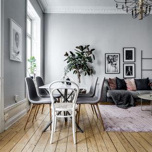Foto på ett stort nordiskt vardagsrum, med grå väggar och mellanmörkt trägolv