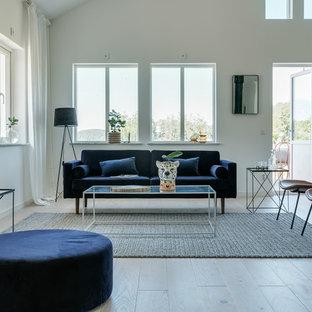 Inredning av ett modernt stort allrum med öppen planlösning, med vita väggar, beiget golv och ljust trägolv