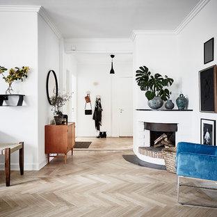 Idéer för att renovera ett skandinaviskt vardagsrum, med vita väggar, ljust trägolv och en spiselkrans i gips