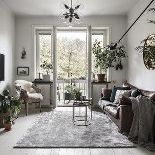 Eklektisk inredning av ett separat vardagsrum, med beige väggar, målat trägolv, en väggmonterad TV och vitt golv