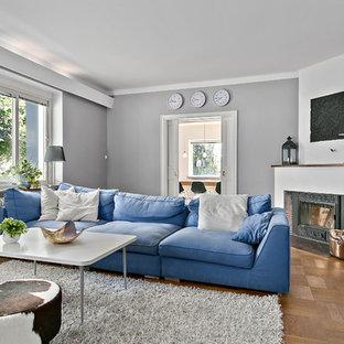 Idéer för ett mellanstort skandinaviskt separat vardagsrum, med grå väggar, ljust trägolv och en öppen hörnspis