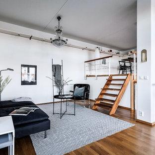 Exempel på ett nordiskt allrum med öppen planlösning, med vita väggar, mellanmörkt trägolv och brunt golv