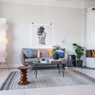 Ejemplo de salón para visitas abierto, nórdico, grande, sin televisor, con paredes beige, suelo de madera clara y estufa de leña