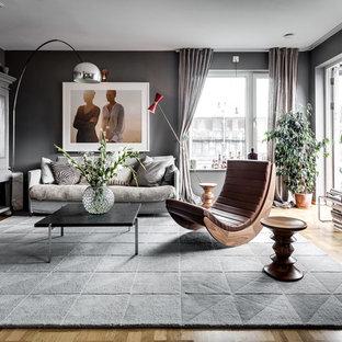 Großes, Repräsentatives, Offenes Skandinavisches Wohnzimmer ohne Kamin mit grauer Wandfarbe, verstecktem TV und braunem Holzboden in Stockholm