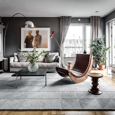 Living room - large scandinavian formal and open concept medium tone wood floor living room idea in Stockholm with gray walls, a concealed tv and no fireplace