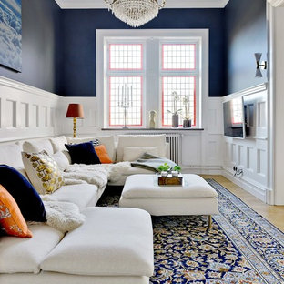 Ejemplo de salón para visitas tradicional, grande, con paredes azules, suelo de madera clara y televisor colgado en la pared