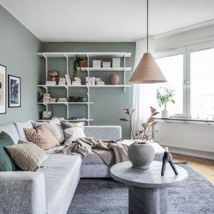 Inspiration för nordiska vardagsrum, med gröna väggar, mellanmörkt trägolv och brunt golv