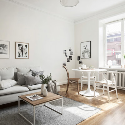 Example of a danish open concept medium tone wood floor living room design in Stockholm with white walls