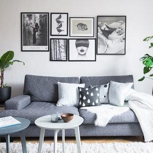 Nordisk inredning av ett mellanstort allrum med öppen planlösning, med ett finrum, grå väggar och ljust trägolv