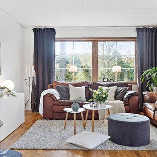Bild på ett mellanstort skandinaviskt separat vardagsrum, med vita väggar, mellanmörkt trägolv, en öppen vedspis, en spiselkrans i gips, ett finrum och brunt golv
