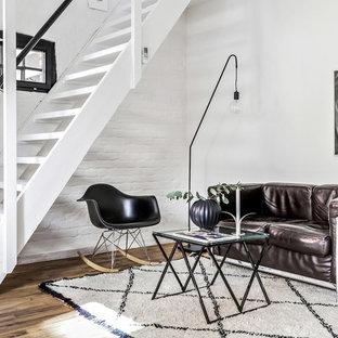 Foto på ett nordiskt separat vardagsrum, med vita väggar och mellanmörkt trägolv