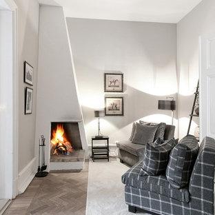 Klassisk inredning av ett litet separat vardagsrum, med vita väggar, en öppen hörnspis, en spiselkrans i gips, ljust trägolv och beiget golv