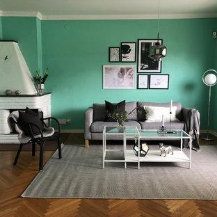 Bild på ett stort funkis separat vardagsrum, med gröna väggar, mellanmörkt trägolv, en öppen hörnspis, brunt golv och en spiselkrans i tegelsten