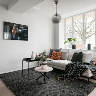 Skandinavisk inredning av ett litet separat vardagsrum, med vita väggar, laminatgolv, beiget golv och en väggmonterad TV