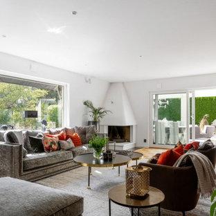 Idéer för ett klassiskt allrum med öppen planlösning, med vita väggar, mellanmörkt trägolv, en öppen hörnspis och brunt golv