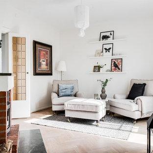 Bild på ett minimalistiskt separat vardagsrum, med vita väggar, ljust trägolv, en standard öppen spis och en spiselkrans i gips