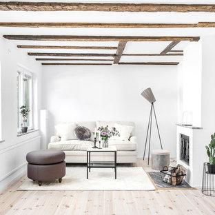 Inspiration för ett mellanstort skandinaviskt separat vardagsrum, med vita väggar, ljust trägolv, en standard öppen spis, en spiselkrans i gips och beiget golv