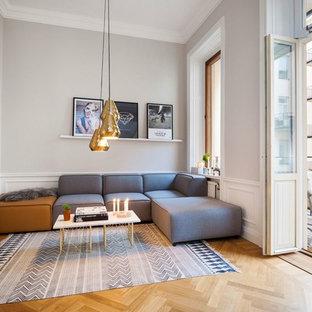 Foto di un grande soggiorno nordico aperto con pareti grigie, pavimento in legno massello medio, nessun camino, TV a parete e sala formale