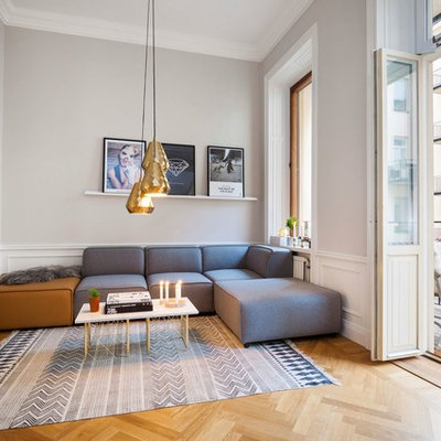 Example of a large danish formal and open concept medium tone wood floor living room design in Stockholm with gray walls, no fireplace and a wall-mounted tv