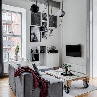 Inredning av ett industriellt mellanstort vardagsrum, med vita väggar, mellanmörkt trägolv, en väggmonterad TV och brunt golv