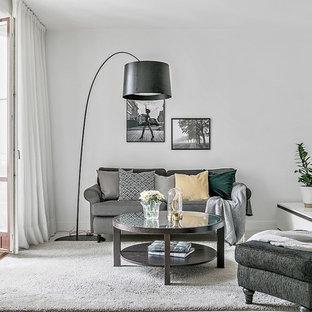 Skandinavisk inredning av ett mellanstort vardagsrum, med vita väggar, en fristående TV och grått golv