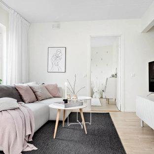 Inspiration för ett mellanstort minimalistiskt allrum med öppen planlösning, med vita väggar, ljust trägolv, en fristående TV och beiget golv