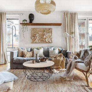 Bild på ett skandinaviskt vardagsrum, med vita väggar, mellanmörkt trägolv och brunt golv
