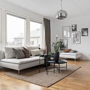 Minimalistisk inredning av ett mellanstort allrum med öppen planlösning, med vita väggar, mellanmörkt trägolv och beiget golv