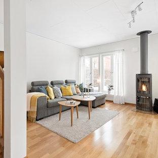 Idéer för att renovera ett funkis vardagsrum, med ett finrum, vita väggar, mellanmörkt trägolv, en öppen vedspis och brunt golv
