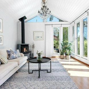 Bild på ett mellanstort vintage separat vardagsrum, med ett finrum, vita väggar, ljust trägolv, en spiselkrans i metall, beiget golv och en dubbelsidig öppen spis
