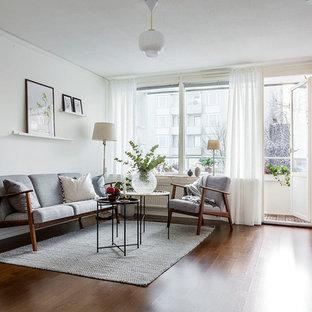 Idéer för att renovera ett skandinaviskt vardagsrum, med vita väggar, mörkt trägolv, en väggmonterad TV och brunt golv