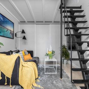 Idéer för nordiska loftrum, med ljust trägolv, beiget golv, grå väggar och en väggmonterad TV