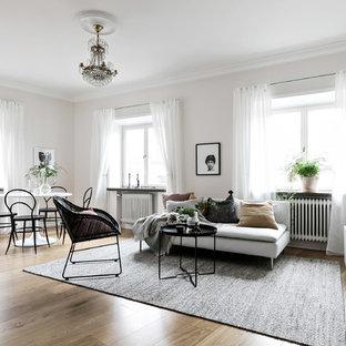 Idéer för att renovera ett mellanstort minimalistiskt allrum med öppen planlösning, med vita väggar, mellanmörkt trägolv och brunt golv